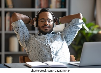 Relaxed african business man wear wireless headphones enjoy listen music with eyes closed hand behind head sit at work desk, young worker take break in office feel peace of mind stress relief concept