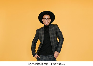 ec6d8bde5e6 Relaxed african guy in vintage checkered suit smiling on yellow background.  Studio shot of excited