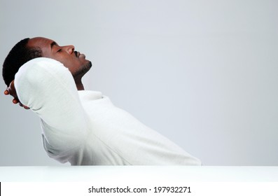 Relaxed african man sleaping at his workplace on gray background