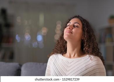 Femme arabe détendue respirant de l'air frais assise sur un canapé dans le salon la nuit à la maison