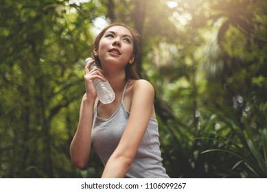 Relaxed Asian Beautiful woman in grey vest shirt holding a bottle of water at green forest background. Thirsty, Resting. Smiling Face. Freshness.