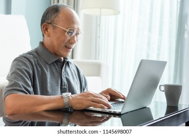 Relaxed Asian Senior man using laptop at his house. Happy Elderly Male laughing. Retirement