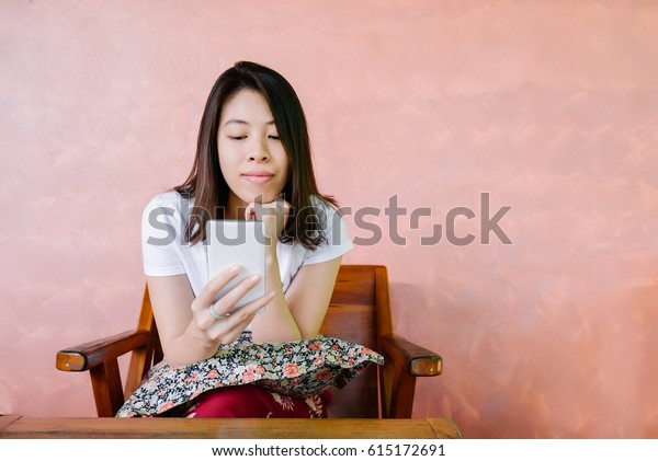 Relaxed asian woman use smart phone reading text message on wooden chair.