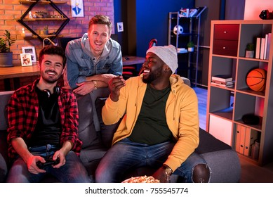 Relaxed atmosphere. Portrait of pleasant stylish young men are sitting on sofa while looking at camera with joy. African positive guy is looking aside with smile while his friend holding joystick