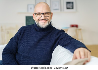 Relaxed attractive bald middle-aged man wearing glasses with a friendly smile sitting on a sofa in his living room smiling at the camera