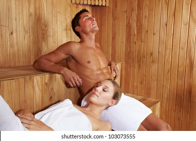 Relaxed attractive couple enjoying peace in sauna