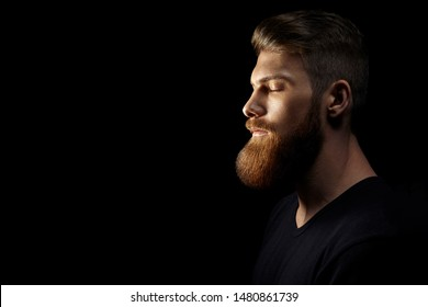 Relaxed attractive male model meditates and tries to relax for minute, keeps eyes shut, dreams about something, isolated over black background Calm peaceful atmosphere.
