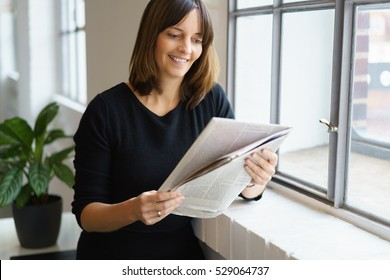 Relaxed attractive woman standing reading a newspaper leaning on the sill of a window smiling with pleasure