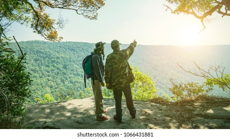 Relaxed backpacker traveler talk with guide or park ranger about traget of point interest in deep forest,feel free and happy.Concept of vacation,freedom,happiness,enjoyment ,summer and well being.