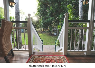 Relaxed balcony (porch) on old Queenslander type home with quaint decorations, furniture and pot plants for relaxed outdoor living.