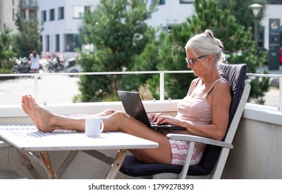 Relaxed barefoot senior woman sitting and typing on a laptop computer outside on a balcony in modern residential building complex with her feet up on a table. Working from home concept.