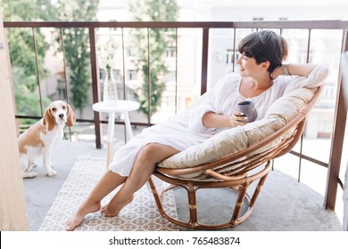 Relaxed barefooted girl in white dress sitting in chair on balcony and holding cup of tea. Adorable brunette woman drinking coffee on terrace and looking with smile at beagle dog.