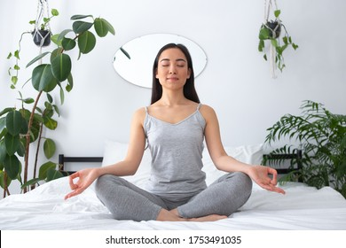 Relaxed beautiful lady is sitting on bed in lotus position with close eyes and developing consciousness