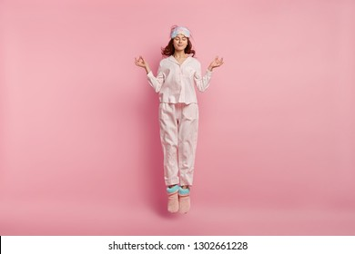 Relaxed beautiful woman meditates before having sleep, dressed in cotton pyjamas, warm chuni, eyemask, jumps against pink background, enjoys calm domestic atmosphere. Restful girl in nightsuit