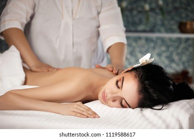 Relaxed beautiful young woman receiving massage in spa salon. Beauty treatment