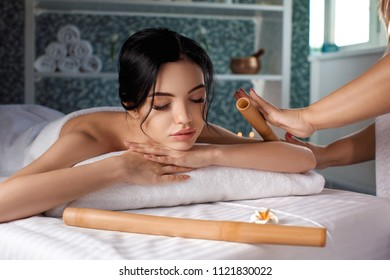 Relaxed beautiful young woman receiving bamboo roller massage in spa salon. Beauty treatment