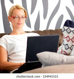 Relaxed, beautiful young woman sitting on sofa, using netebook.