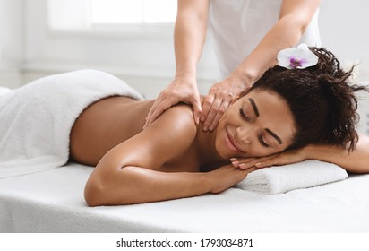 Relaxed black girl enjoying full body massage at new spa, side view