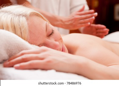 A relaxed blond woman receiving a percussive massage in a spa