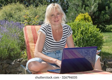 Relaxed blonde middle aged woman is sitting outdoors on the sun lounger with open notebook and is looking to the camera. Garden with blooming lavender is in the background.