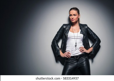cfb5c4d9a16 relaxed blonde woman in leather jacket looks away to a side while standing  with hands on