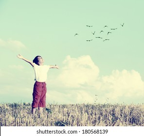 Relaxed boy breathing fresh air on a meadow with birds flying in background sky