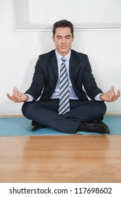 Relaxed business manager doing yoga in his office