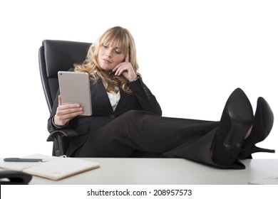 Relaxed business woman holding a tablet reading with her feet up the table