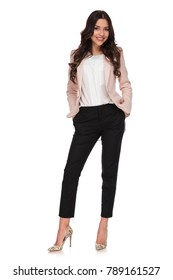 84a32a441117 relaxed business woman standing with hands in her pockets on white  background
