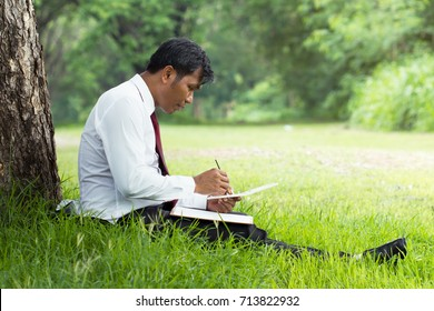 Relaxed businessman draw a picture under the tree in the park.