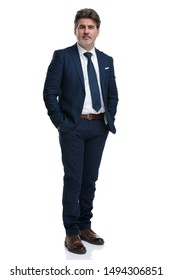 Relaxed businessman holding both hands in his pockets while wearing an elegant blue suit and standing on white studio background