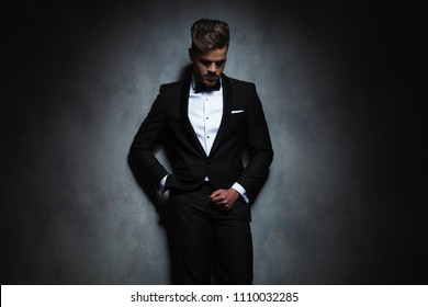 relaxed businessman leaning against a black wall while looking down. He is wearing a black tuxedo while standing with hand in pocket