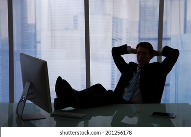 Relaxed businessman sitting with feet up at computer desk in office