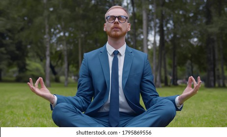 Relaxed businessman sitting on lawn doing meditation in city park. Young man in formal wear sitting on grass in lotus pose meditating outdoors after stressful day at work