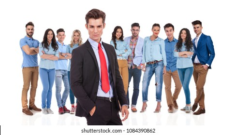 relaxed businessman standing with hand in pocket in front of his young casual team on white background. He is wearing a black suit while his team are wearing blue shirts