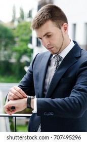 Relaxed businessman standing on balcony of his apartment and looks at the watch