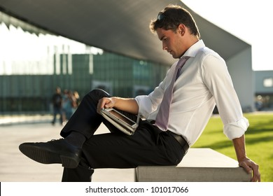 Relaxed businessman using his PC tablet while sitting on a bench