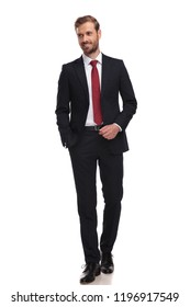 relaxed businessman walking on white background and looking to side while smiling, full length picture