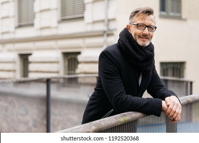 Relaxed businessman in warm coat and scarf standing leaning on a bridge railing in town with a smile