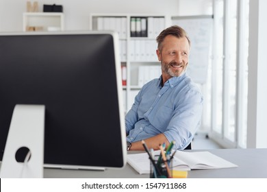 Relaxed businessman watching in amusement as he sits back in his chair looking back through an office window