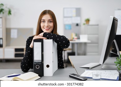 relaxed businesswoman leaning on black and white folders