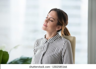 Relaxed calm female office worker resting sitting in ergonomic chair lounging at work dreaming or good future, serene happy businesswoman feels no stress free relief breathing fresh air at workplace
