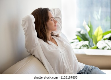 Relaxed calm woman resting breathing fresh air feeling mental balance enjoying wellbeing at home on sofa, satisfied young lady taking pleasure of stress free weekend morning stretching on couch - Shutterstock ID 1126189853