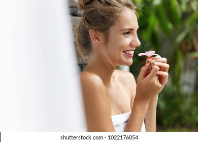 Relaxed carefree young female with happy expression wrapped in towel, dreams about something pleasant while smells oudour flower, going to take bath, poses outdoor in hot tropical country alone