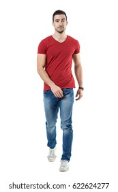 Relaxed casual man in jeans and red t-shirt walking and looking at camera. Full body length portrait isolated over white studio background.