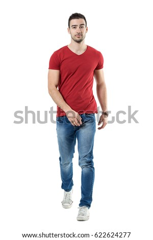 8621e24eeed Relaxed casual man in jeans and red t-shirt walking and looking at camera. Full  body length portrait isolated over white studio background. - Image