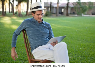Relaxed casual man sitting in park using tablet PC