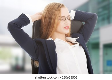 Relaxed caucasian beautiful business woman sitting on a chair.