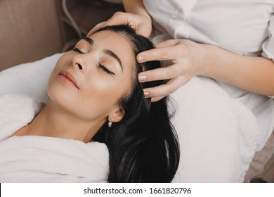 Relaxed caucasian brunette waiting with closed eyes during a spa procedure for her skin and hair