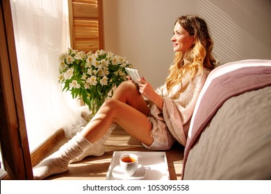 Relaxed Caucasian girl is sitting on a warm floor in pajamas wrapped in a woolen blanket near the window in light. She is enjoying  sunny spring morning. beautiful female in socks drinking morning tea